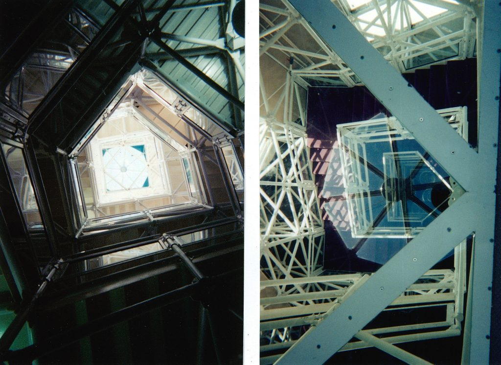 A view looking up the staircase to the tower of the Biosphere 2 Center and a look through the glass floor from the library at the top to the ground floor below.